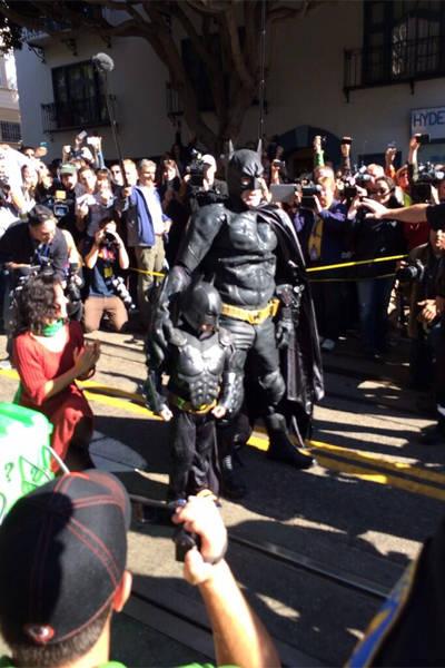 Batkid resgata mulher em rua de Gotham City; multidão acompanha a ação