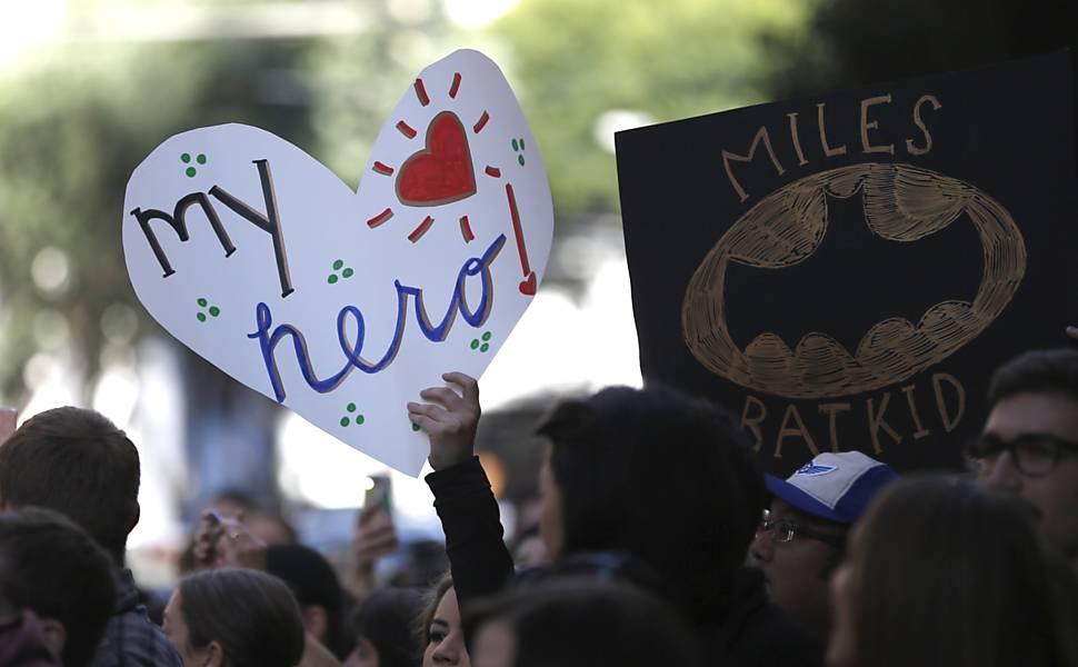 Pessoas exibem cartazes de apoio ao Batkid