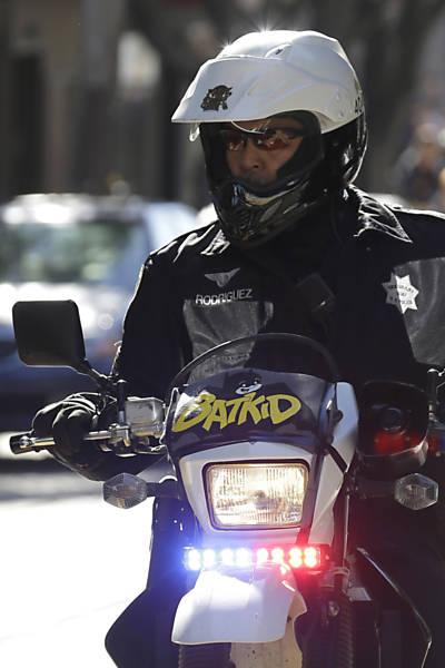 Policial de San Francisco aguarda a chegada do Batkid em sua moto
