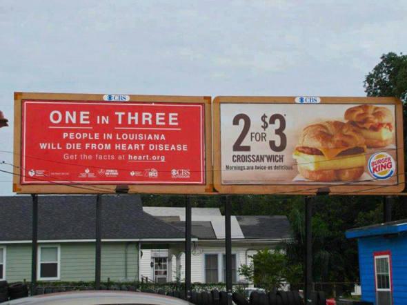 Outdoor do Burger King e ao lado outro: uma a cada três pessoas na Lousiana irão morrer de doenças cardíacas. E no Burger King você pode comprar três sanduíches gordurosos pelo preço de um. Você comeria um hambúrguer depois de uma mensagem dessas ?