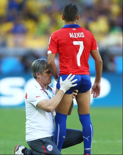 Chileno Alexis Sanchez recebe uma atenção especial do fisioterapeuta, antes do início da prorrogação, no jogo de oitavas de final contra o Brasil, no Mineirão Foto: Jeff Gross