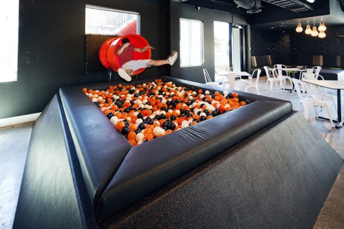 """iSelect, Melbourne Austrália. O escritório da iSelect lembra um playground. Ele possui diversos ambientes de lazer e de trabalho, entre eles uma sala de reuniões circular que ficou conhecida entre os funcionários como """"sala do interrogatório"""".  Há espaço para dormir, correr, jogar futebol e receber uma boa massagem. Tudo !"""