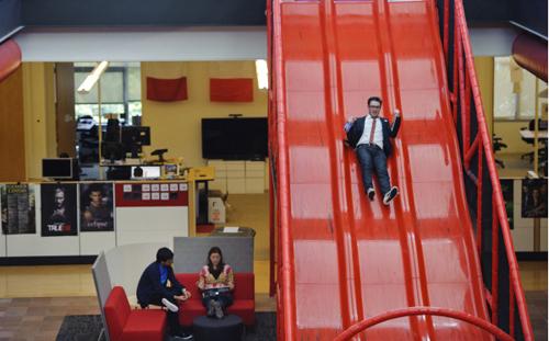 """YouTube, San Bruno (EUA). Teto com trepadeira, parede para escalar, campo de mini-golfe…  O escritório do YouTube faz justiça à fama do """"pai Google"""". Com o amplo tobogã que você vê acima, dá pra disputar corridas nos intervalos de trabalho."""