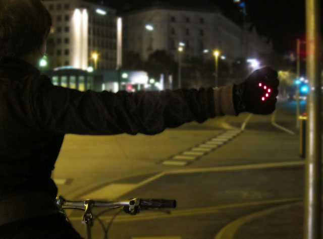 Luva sinalizadora com led. Possui condutores na ponta dos dedos e na palma das mãos e ao fechar o punho e juntar dedos e palma, as luzes se acendem em forma de seta.